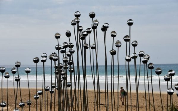 Silver sculpture in front of waves at Lorne Sculpture Biennale